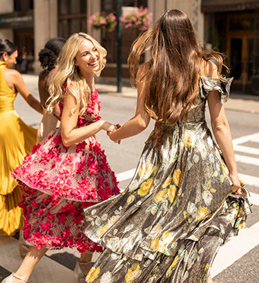 Two wedding guests in vibrant, floral dresses smile and walk across the street on a crosswalk.