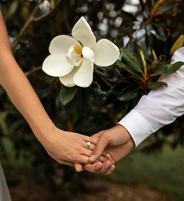 A bride holds hands with another with a beautiful white flower above their hands.