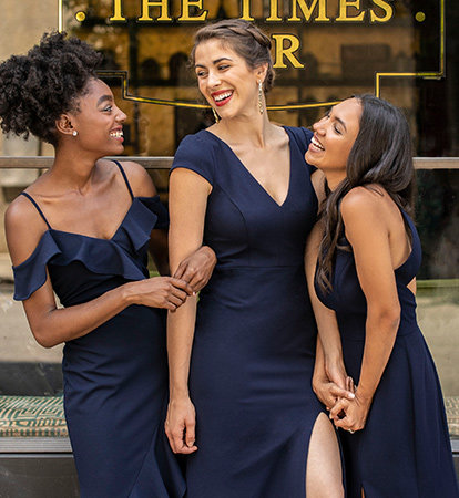 Bridesmaids wearing black dresses laugh and smile at each other.