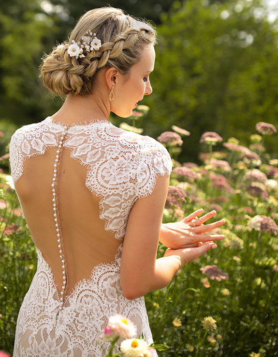 Bride admires ring while standing in a wildflower field.