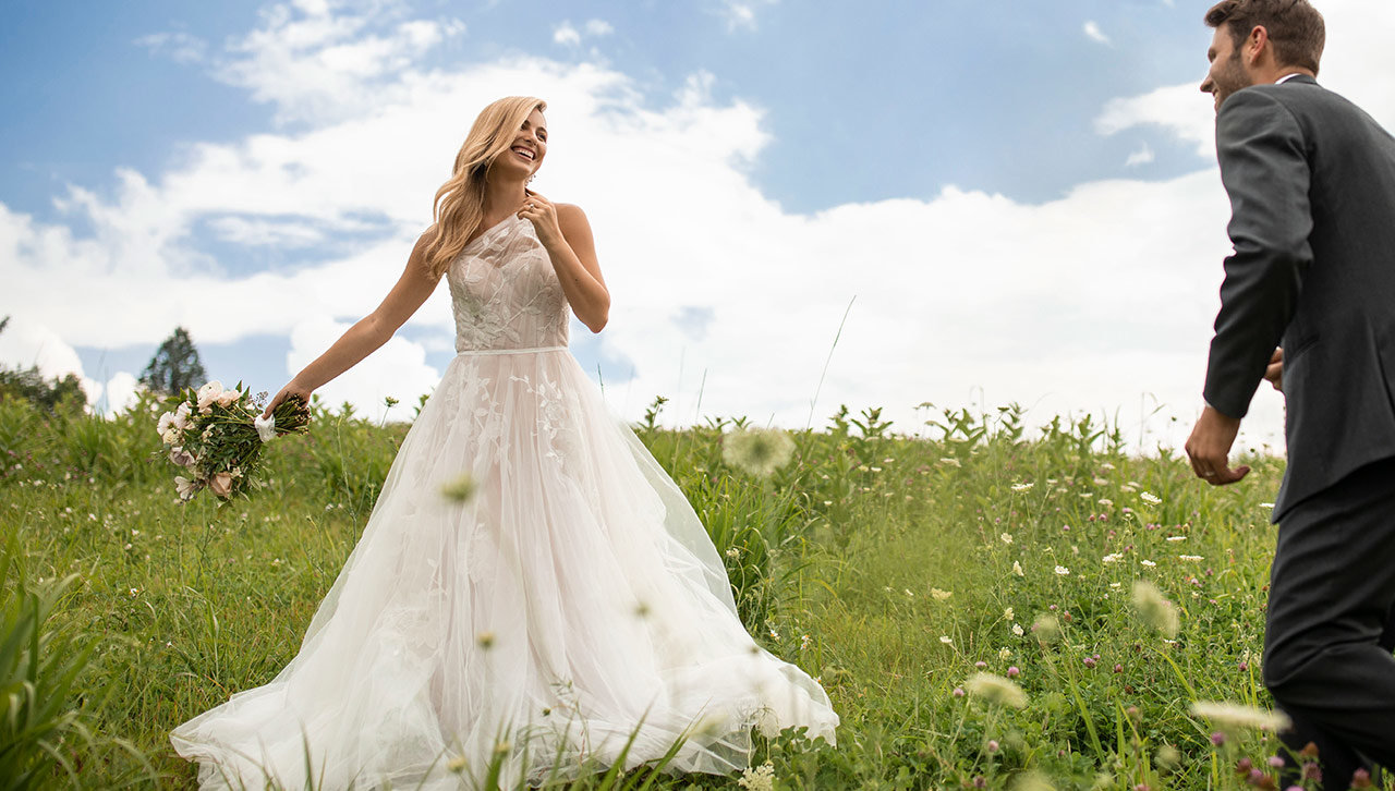 Bride smiles at groom while wearing a ballgown in an open grassy field.