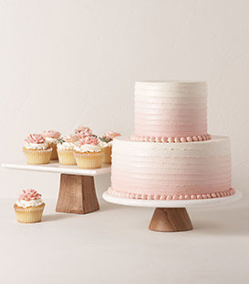 Cupcakes and a cake are set on marble cake stands.