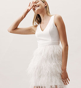 A model smiles and laughs in a feathery little white dress.