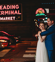 Bride and groom smile together in Reading Terminal market.