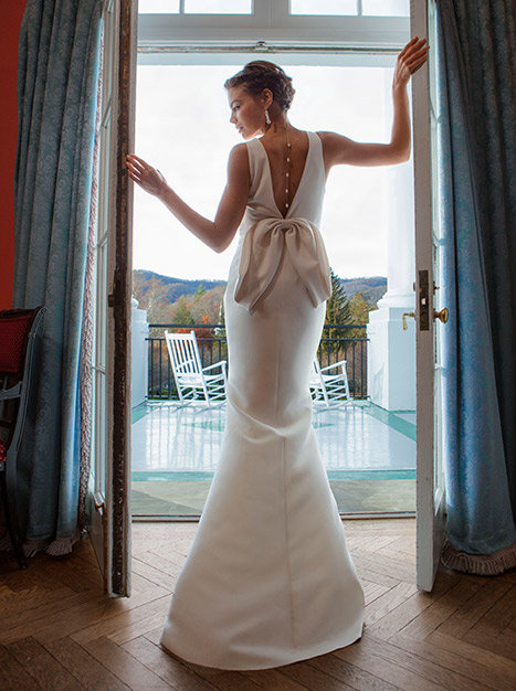 Bride standing in doorway with back to camera showing off the deep-v back detail of the Branwell Gown.