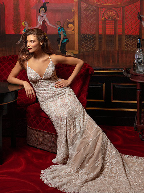 A bride in a chair leaning on table to the side in the long flowing beaded Dixie Gown.