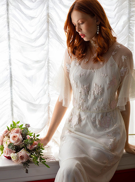 Bride sitting on window sill looking at the pink and white flower bouquet in hand in the flowey and lighly embroidered Avila Gown.