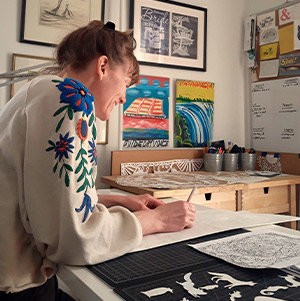 Artist Annie Howe sitting at a table cutting animal shapes out of white paper.