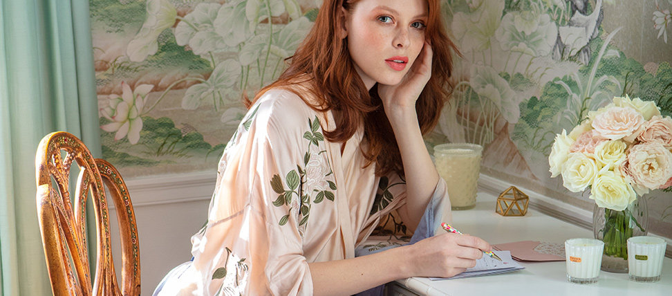 Bride-to-be sitting at desk in floral robe writing invitations.