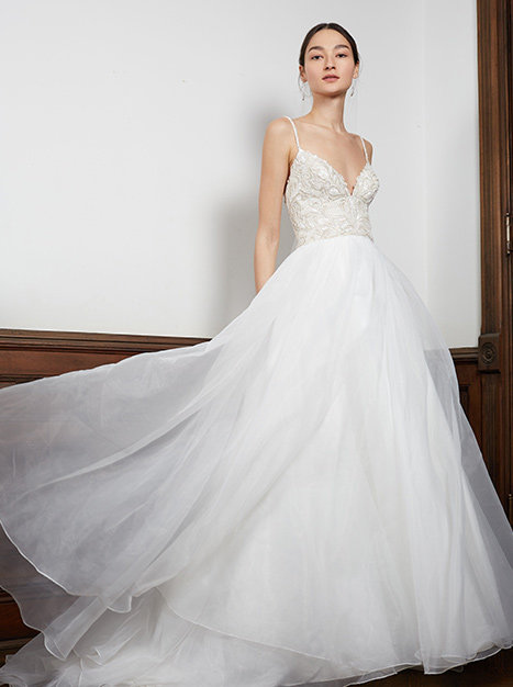 Bride standing against white wall in wide layered and flowing train of the Hemingway Gown.