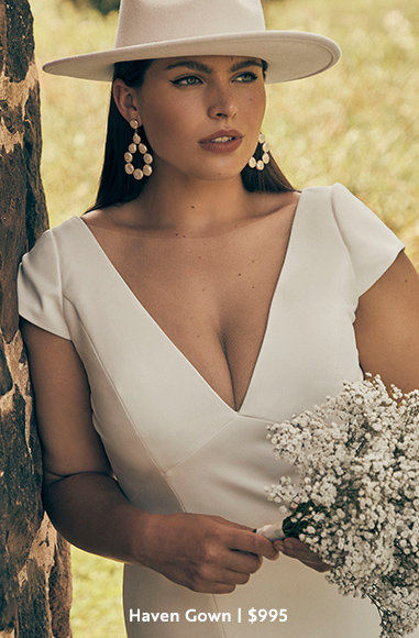Bride holding a bouquet of posies in a sun hat and the Haven Gown from BHLDN in plus sizes at $995.