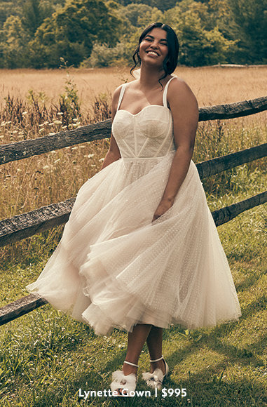 Bride in layered tulle Lynette Gown with a corset style top in plus size next to fence, $995.