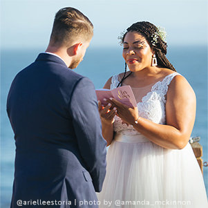 Artist Arielle Estoria standing with to be husband reading vows from a pink notebook with gold text on the cover.